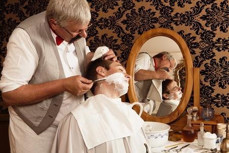 barbero: Barbero antiguo afeitado a un cliente con crema de afeitar Foto de archivo