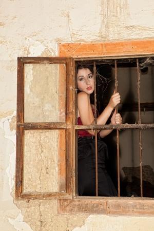 detenuti: Bella donna dietro le sbarre arrugginiti in una vecchia casa abbandonata Archivio Fotografico