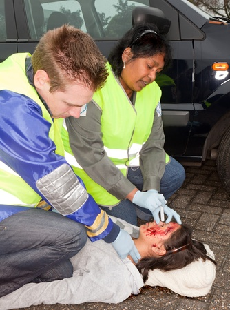 fatal: Paramedics checking a woman injured during a car accident (the sleeve badges have been replaced by a non existing logo)