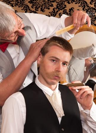 hombre fumando puro: Cliente elegante en una recreación histórica de una peluquería victoriana Foto de archivo