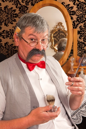 Proud barber showing his tools in a historical reenactment of a victorian barbershop photo