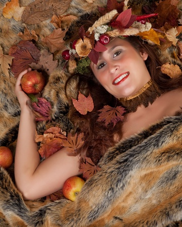 Fall woman with garland of leaves and autumn fruit in her hair lying on a fur blanket photo