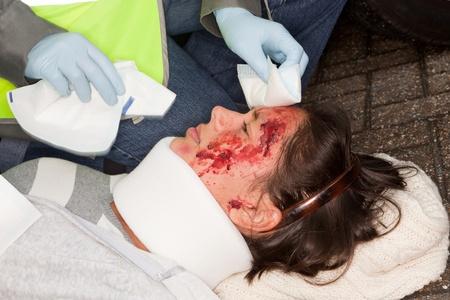 primeros auxilios: Mujer con rostro herido, siendo ayudado por un param�dico