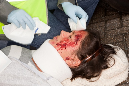 bleeding: Woman with wounded face being helped by a paramedic Stock Photo