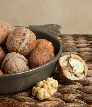 pewter: Vintage pewter bowl filled with rustic autumn walnuts