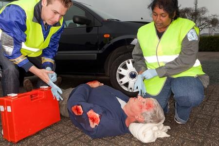 hemorragias: Param�dicos poner guantes est�riles para atender a una v�ctima de accidente de coche (las insignias de manga han sido sustituidas por un logotipo no existente) Foto de archivo