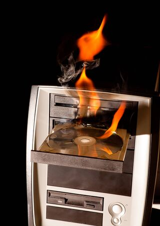 Computer on fire with flames in the cd drive photo