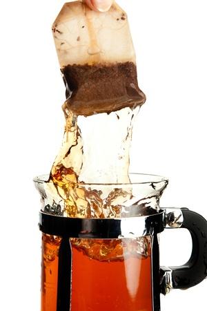 teabag: Hot tea splashing when a hand removes the tea bag