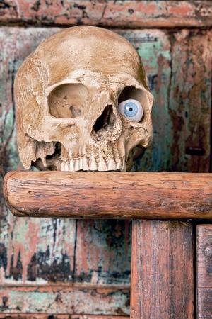 macabre: Artificial glass eye in an antique human skull