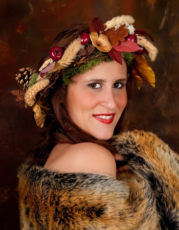 Fall woman with garland of leaves and autumn fruit in her hair photo
