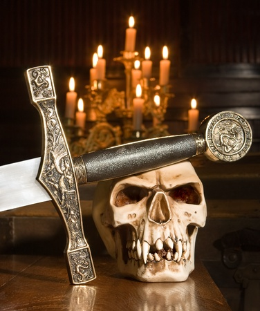 medieval sword: Medieval sword and skull lit by candles Stock Photo
