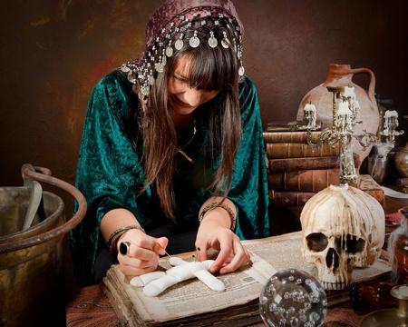 Voodoo gitana poner agujas en una muñeca echando un hechizo o una maldición sobre (el libro es 300 años, sin problemas de derechos de autor)