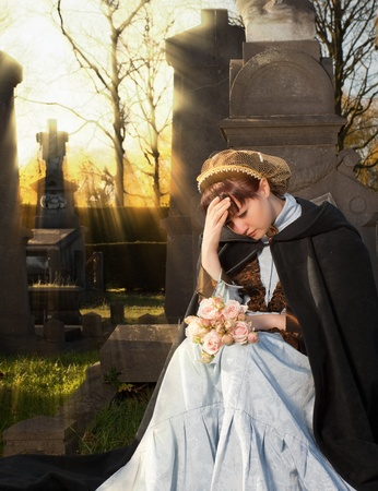 Young Victorian widow mourning on a tombstone at Halloween photo