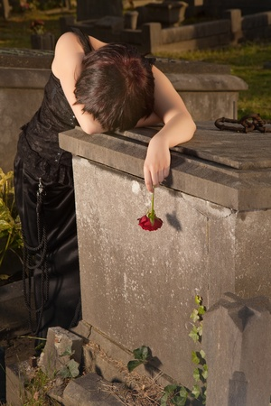 Crying gothic girl leaning on a tombstone holding a rose photo