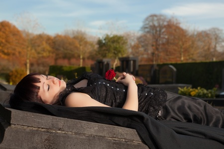 Beautiful dead woman lying in gothic dress on a tomb photo