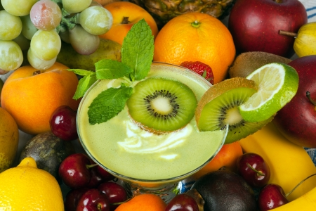 mixed berries: Kiwi smoothie surrounded by an abundance of summer fruits Stock Photo