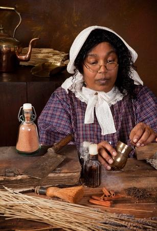 herbolaria: Campesina victoriana, mezcla de hierbas e ingredientes en una cocina antigua Foto de archivo