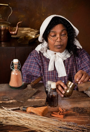 herbalist: Victorian peasant woman mixing herbs and ingredients in an antique kitchen