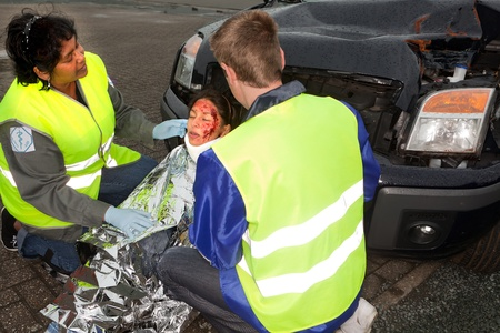 Two paramedics helping a young injured victim of a car accident (the sleeve badges have been replaced by a non existing logo) photo