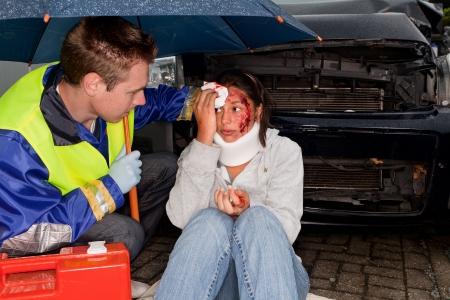 Paramedic caring for an injured woman under an umbrella photo