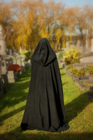 widow: Woman with victorian cape visiting a very old graveyard Stock Photo