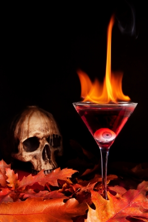 fire skull: Burning halloween cocktail with skull and glass eye Stock Photo