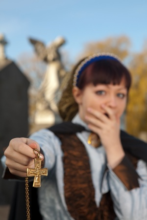 diabolist: Young victorian woman trying to keep evil away in a graveyard Stock Photo