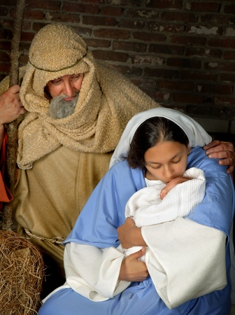 Live Christmas nativity scene reenacted in a medieval barn (the baby is a doll) Stock Photo