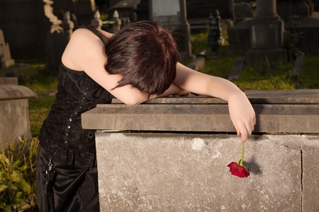 widow: Halloween woman in gothic dress crying on a tomb