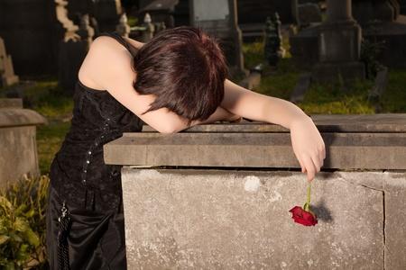 tumbas: Mujer de Halloween vestido de g�tico llorando en una tumba