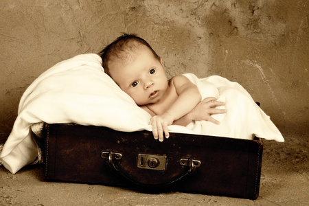Little newborn baby of 18 days old in an old vintage leather suitcase photo