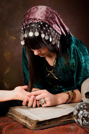 wicca: Young palmister reading the future in a hand (the book is 300 years old, no copyright problems) Stock Photo