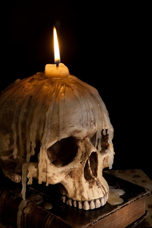 Halloween image with a burning candle on an ancient skull Stock Photo - 10673523
