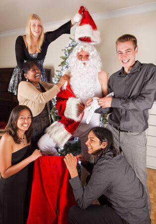 vistiendose: Re�rse de la familia ayudando a su padre a vestirse con su traje de Santa Claus Foto de archivo