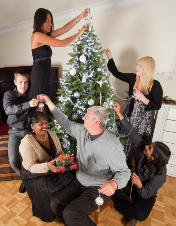 decorating christmas tree: Happy family decorating together the christmas tree Stock Photo