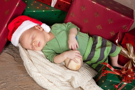 Christmas gifts surrounding a little newborn baby photo