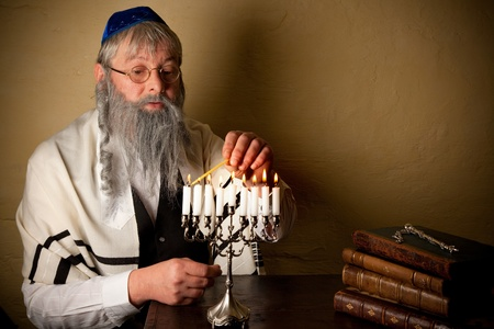 Old jewish man with beard lighting candles for hannukah photo