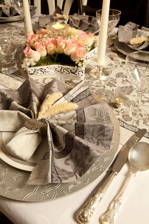 antique dishes: Pink flower arrangement on a grey tone fancy christmas table with antique cutlery