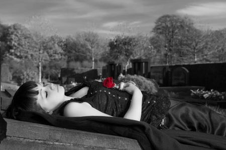 Gothic widow lying on a tombstone with a red rose