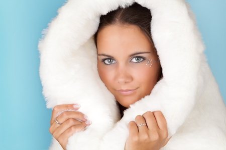 Winter girl with white fur hat wearing warm fur coat Stock Photo