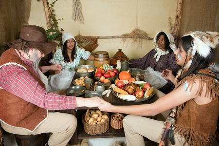Reenactment scene of the first Thanksgiving Dinner in Plymouth in 1621 with a Pilgrim family and a Wampanoag Indian Stock Photo - 10761461
