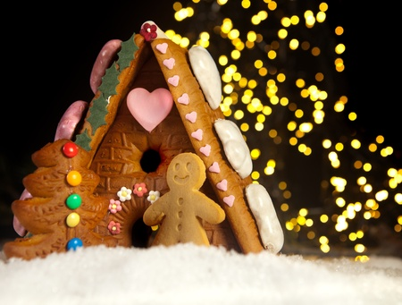 Funny gingerbread man in front of his candy house Stock Photo - 10842378
