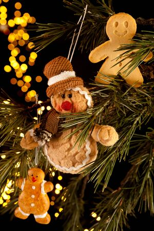 fake christmas tree: Three gingerbread men hanging in a christmas tree, two fake and one real cookie