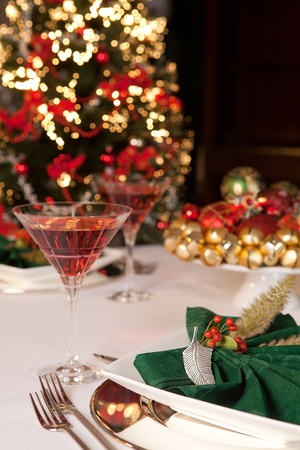 Fancy green napkins and baubles in front of a blurred christmas tree Stock Photo