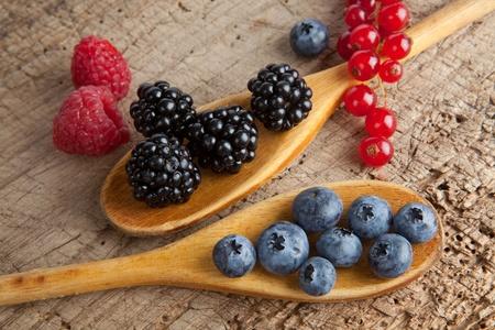 Autumn berries and wooden spoons on an old board Stock Photo - 10842385