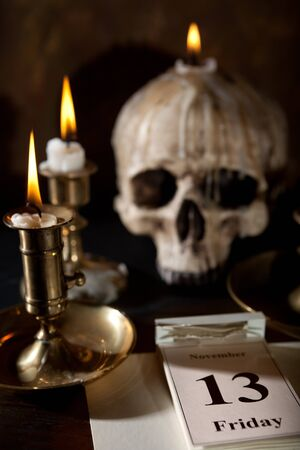 superstitions: Friday 13th on a calendar with candles and a creepy skull