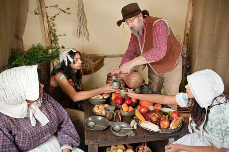 Reenactment scene of the first Thanksgiving Dinner in Plymouth in 1621 with a Pilgrim family and a Wampanoag Indian Stock Photo - 10842435