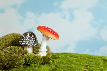 Artifical toadstools standing on real moss as an background for fairytale scenes photo