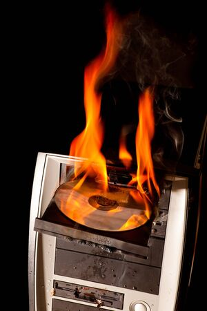 broken computer: CD drive and entire computer on fire Stock Photo