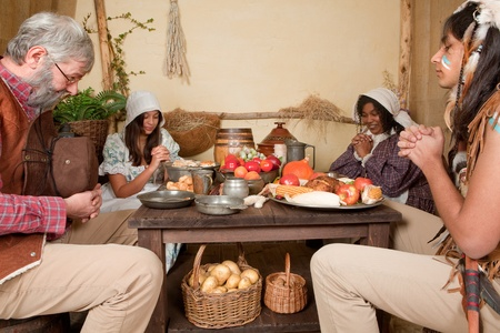 Reenactment scene of the first Thanksgiving Dinner in Plymouth in 1621 with a Pilgrim family and a Wampanoag Indian Stock Photo - 10916523